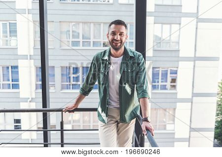 Just relax. Portrait of happy bristled man is leaning on handrail on cityscape background. He is looking at camera with joy