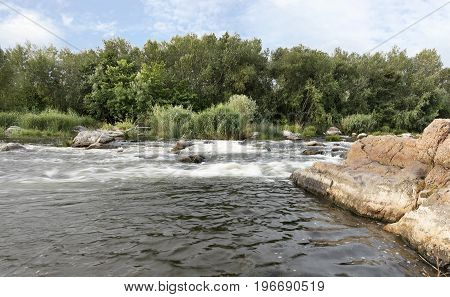 The river Southern Bug in the summer - fast river flow rocky shores rapidsbright green vegetation and a cloudy blue sky