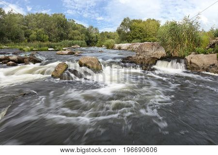 The rapid flow of the river rocky shores rapids bright green vegetation and a cloudy blue sky in the summer. Southern Bug. Ukraine