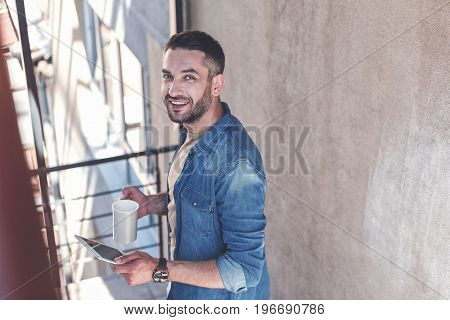 Happy smile. Top view of cheerful adult bearded man is standing on steps with tablets and espresso. He is looking at camera with joy. Copy space in the right side