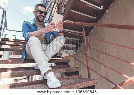 Street style. Low angle of delightful stylish bristled guy in sunglasses is sitting on steps with smile while reading information using modern tablet. Copy space in the right side