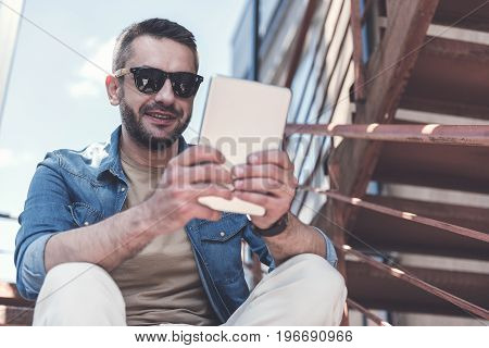 Sunny day. Joyful trendy man in sunglasses is sitting on steps outdoors and holding modern tablet while reading news. Focus on reflection in glasses. Copy space in the right side