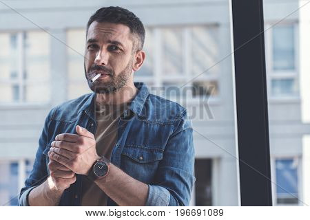 Bad habits. Portrait of serious bearded man is smoking cigarette and looking at camera thoughtfully. Copy space in the right side