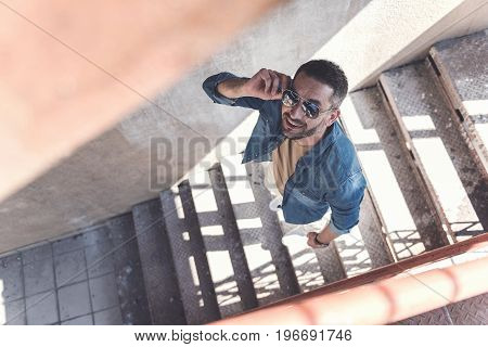 Positive emotions. Top view of cheerful stylish man is standing on steps and touching his sunglasses while looking at camera with smile. Copy space in the left side