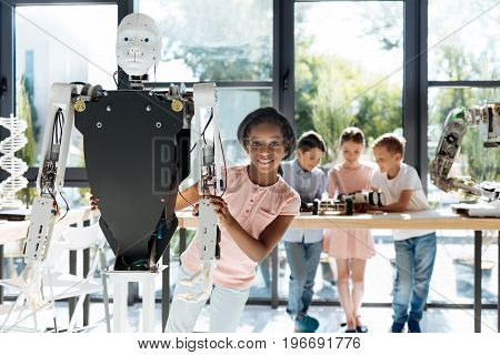 Futuristic friend. Pretty pre-teen girl standing behind a human robot, hugging it and smiling at the camera while her peers examining robotic models on the table in the background