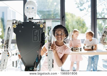 Future new friend. Adorable pre-teen girl hugging a big human robot from behind and posing for the camera with a broad smile
