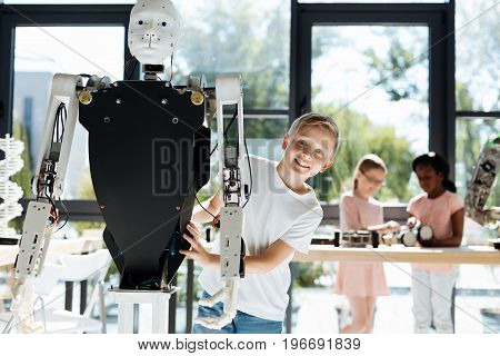 Beautiful smile. Adorable little boy standing behind a big human robot with black chest and looking at the camera with a charming smile