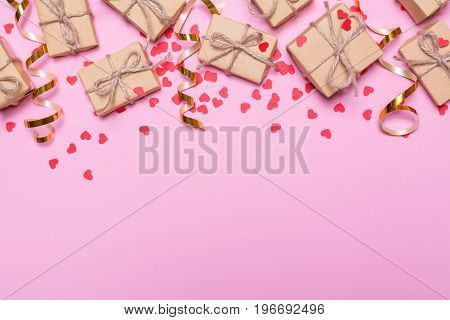 Gift boxes wrapped in kraft paper on a pink background. Confetti hearts and gold ribbons, festive decor. Flat lay design, top view