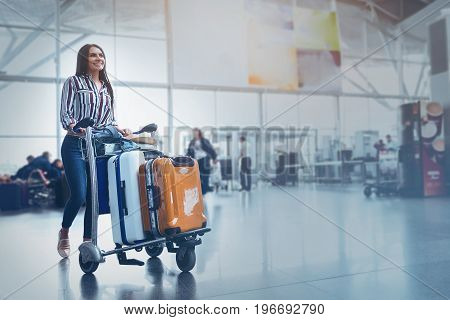 Happy female passenger is walking down airport-foyer with luggage on convenient cart. She smiling glancing ahead. Copy space on right side