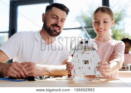 Scrutinizing carefully. Beautiful fair-haired girl holding a new white robot and examining its back part together with her teacher, both looking at it intently