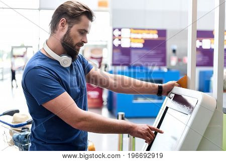 Serious male passenger is doing self service check-in on certain device. He typing on screen