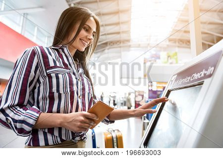 Cheerful lady is using device in airport for self service check-in. She typing on screen and glancing at it with smile. Low angle
