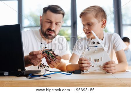 Necessary help. Pleasant young teacher of robotics holding a bunch of colorful wires and choosing one for a newly constructed robot of his student while the boy observing the process