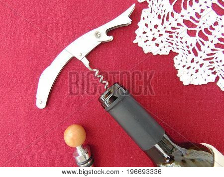 Bottle of red wine with corkscrew on bordeaux red background