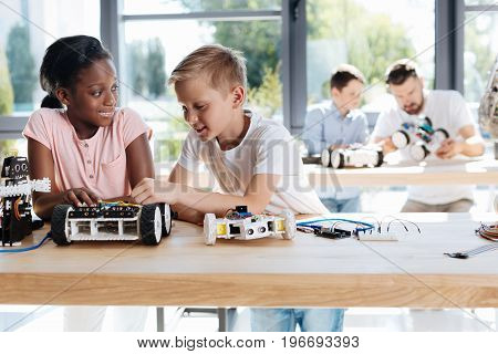 Exchange of ideas. Adorable pre-teen boy and girl standing in the robotics classroom near the table full of robotic parts and sharing their ideas on the construction of a robotic car