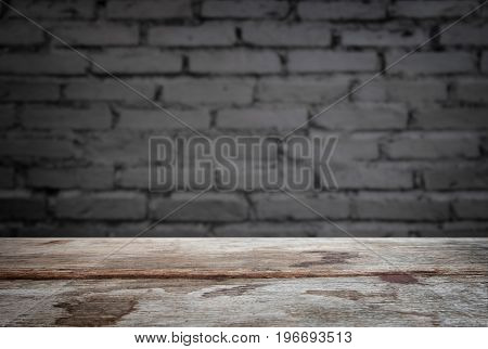 Selected focus empty old wooden table and wall texture or old black brick wall blur background image. for your photomontage or product display.