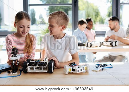 Pleasant chat. Pleasant smiling boy talking to his female friend while constructing a robotic vehicle together during a workshop while their teacher and friends discussing something in the background