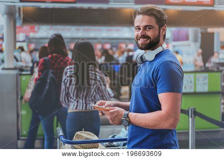 Joyous male passenger is standing in line for check-in. He keeping planting documents and glancing at camera with smile. Portrait