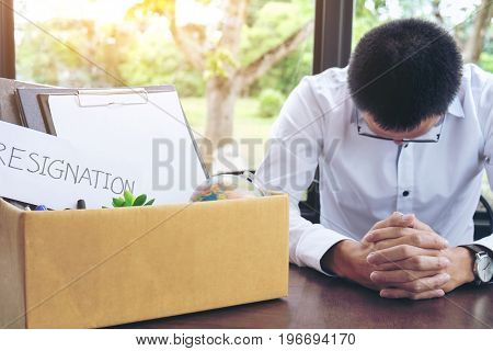 Images of packing up all his personal belongings and files into a brown cardboard box and Businessman has stress to resignation resign concept.