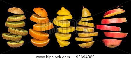 Creative concept with food. Set of sliced fruits isolated on black background. Flying lemon, orange, kiwi, pear, apple. Levity fruit floating in the air