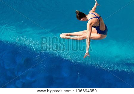 Young woman diving in to the swimming pool high angle view