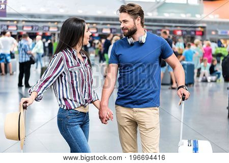 Merry man and woman are holding hands and looking at each other with affable smile. They holding baggage