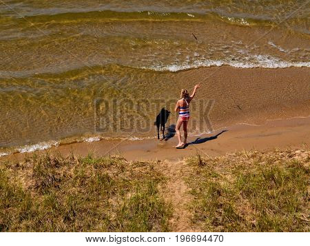 Women playing fetch with her dog on beach Muskegon Michigan