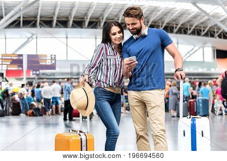 Cheerful couple is looking at screen of smartphone with smile. They are standing in terminal of airport