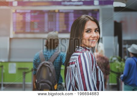 Happy lady is standing afore scoreboard and looking at camera with bright smile. Portrait