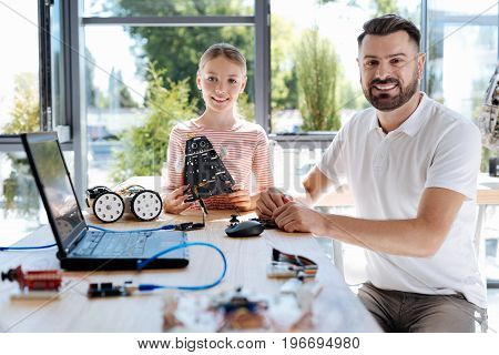 Favorite workshop. Cheerful pre-teen girl holding a cosmic warrior robot model while sitting next to her pleasant robotics teacher, both of them smiling at the camera