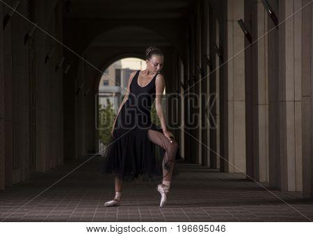Gracefull ballerina posing out of doors. Ballerina dance on a background of columns