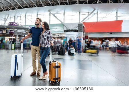 Merry couple is standing together and looking up with bright smile. They are waiting for plane. Copy space on right side
