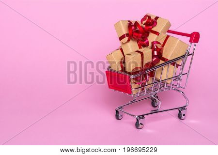 Creative concept with shopping trolley with gifts on a pink background. Gifts wrapped in kraft paper with a red ribbon and bow.