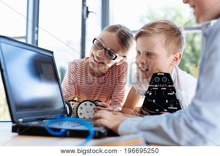 Useful update. Charming pre-teen children being gathered around their friend working on the laptop with the last software update and observing the process