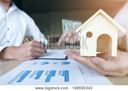 Man sign a home insurance policy on home loans Agent holds home and pointing loan documents. Real Estate concept.