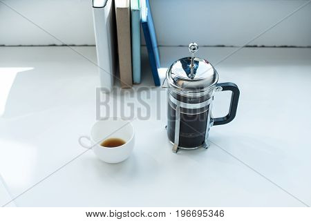 French Press With Coffee Cup Standing On White Desk With Row Of Books