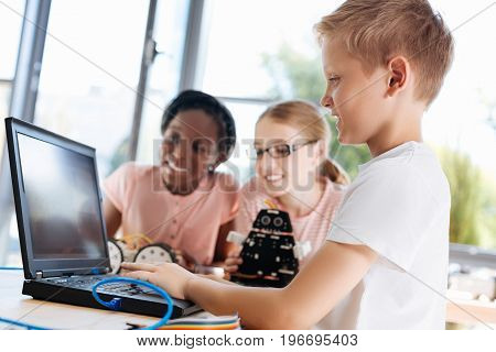Interesting video. Handsome fair-haired boy watching a tutorial video about robotics together with his to female friends
