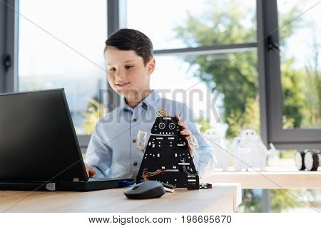 Complete finisher. Charming little boy sitting at the table and using a laptop to finish a setup of a black robot standing on the table