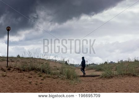 A man walking away from the beach of Kalajoki Finland. The weather was cold and rainy and quickly getting worse. The man is hurrying to a warmer place.