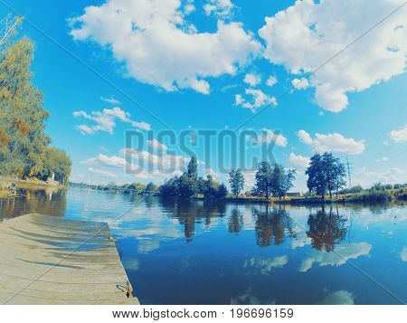 Landscape water river lake mooring surface reflecting mirror sky. Wide angle action camera go pro.