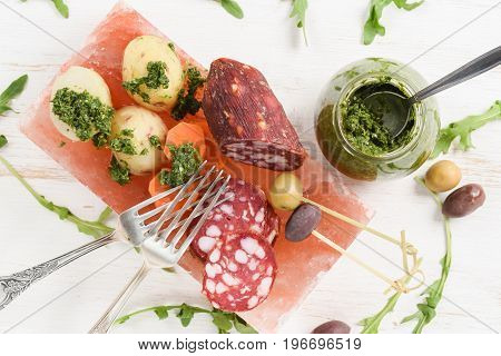 Smoked salami potatoes and olives with green chimichurri sauce and vintage melchior forks. Appetizers served on hymalayan pink salt block top view