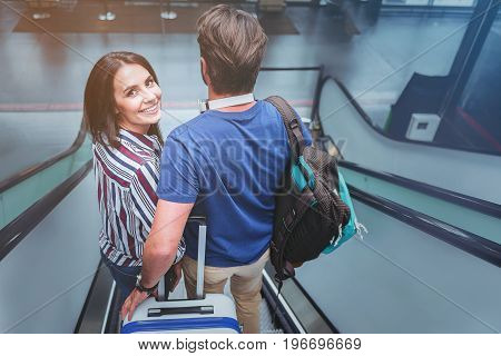 Feeling excitement. Top view portrait of happy delightful young woman is getting down on moving staircase at airport with her lover. Man from the back is holding suitcase and backpack
