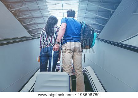 Happy to travel together. Low angle of young lovers from behind are climbing up on escalator at airport with suitcase