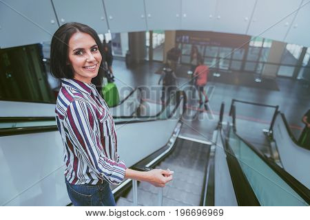 Exciting expectation. Top view portrait of charming tourist girl is standing in international airport on escalator and moving down while looking at camera with joy. Copy space in the right side