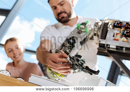 Best performance. Handsome bearded man testing the performance of hand mechanism of a future human robot while the girl looking at the process curiously
