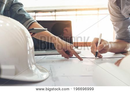 Image of engineer or architectural project two engineering discussing and working on blueprint with architect equipment Construction concept.