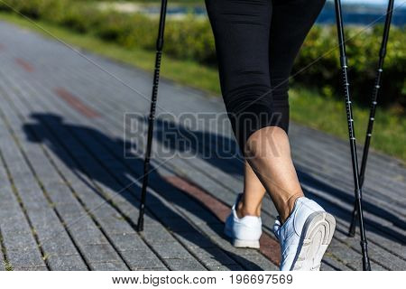 Nordic walking - middle-age woman working out outdoor