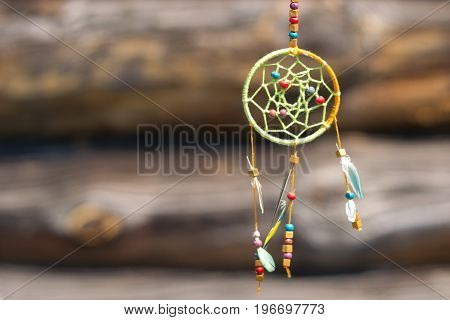 Dream catcher in the wind on a wooden background