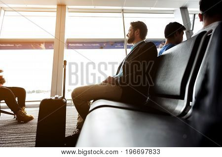 Sunny day. Cheerful bearded man is sitting on bench at waiting hall in international airport. He is looking through window with smile. Copy space in left side