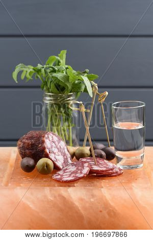 Vodka shot with appetizers: smoked salami fresh arugula green and calamata olives set on hymalayan pink salt block vertical